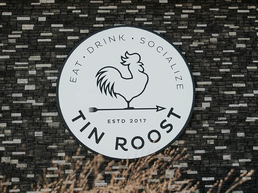 Tin Roost logo on exterior of restaurant